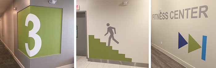 A collection of branded wayfinding signs and wall graphics