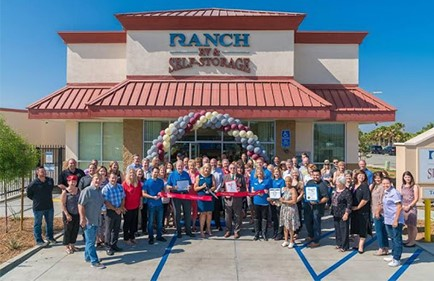 A group of employees at a grand opening gathering for a ribbon-cutting ceremony.