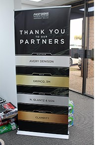 A vertical banner sign thanking sponsors and partners of a business.