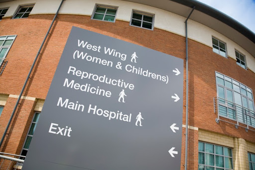 An outdoor wayfinding sign outside a hospital guiding patients to the correct wings.